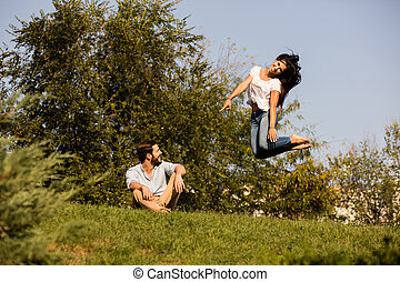 woman jumping up next to her lover with joy - happy and...