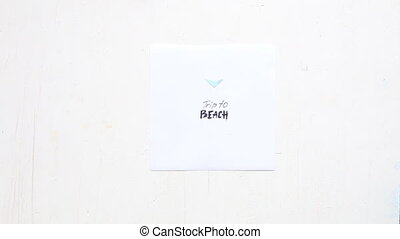 Trip to Beach idea, hand and a piece of paper with the...