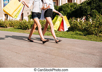 Two women walking along street with bags and coffee cups -...