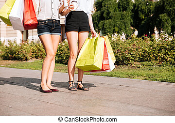 Two young female walking along street with shopping bags -...