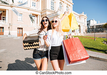 Portrait of two female friends shopping together and walking...