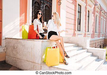 Two happy women with shopping bags on steps - Two happy...