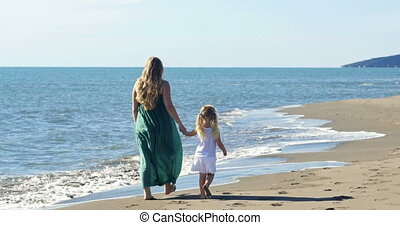 mother and daughter walking on the beach along the sea