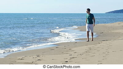 man walking on the beach along the sea