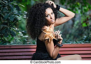 Young african woman siting on bench in park - Black woman...