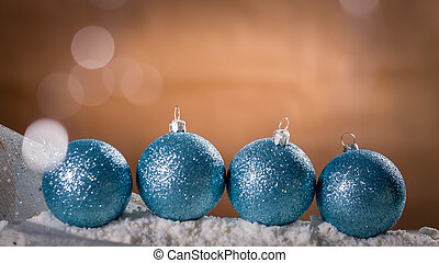 Four turquoise Christmas baubles on snow. Xmas greeting...
