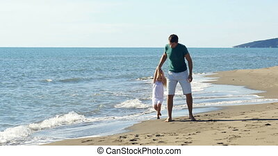 Dad holding daughter's hands and circling on the beach