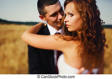Bride looks gorgeous being huged by a groom among the wheat