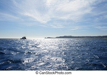Blue Mediterranean sea with fishing boat far in horizon