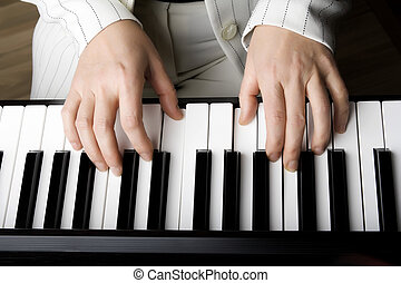 Two hands playing on the piano - Hands of middle-aged women...
