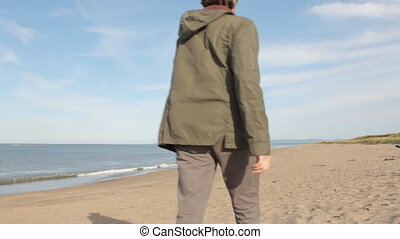 A middle aged man with a beard wearing grey pants, green jacket and yellow boots camera, turning around, looking at the sea thoughtfully and walking on.