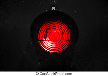 Red traffic light isolated on black background
