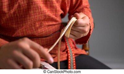 Wickerwork. Close-up view of boy twists rod