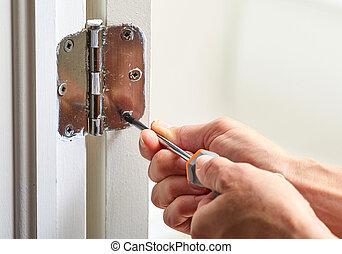 Door hinge installation. - Hands with screwdriver fixing a...