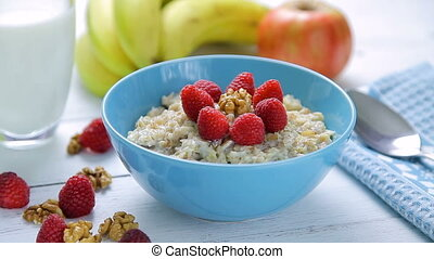 healthy breakfast - oatmeal with fresh, ripe raspberries and walnuts in a bowl standing on a wooden table