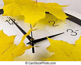Fall back, winter time. Clock with yellow maple leaves.