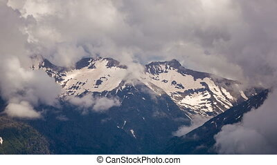 snow-capped mountain peaks - Big clouds over the snow-capped...