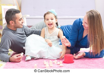 Little Girl And Parents Playing With Toys Together