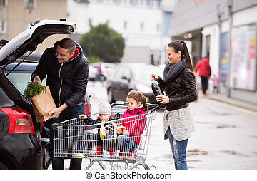Parents pushing shopping cart with groceries and their...