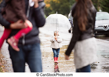Little girl under the umbrella with her family, walking....