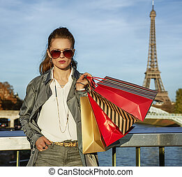 trendy woman in trench coat with shopping bags in Paris,...