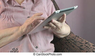 Aged woman 80s holds the silver tablet computer - Aged woman...