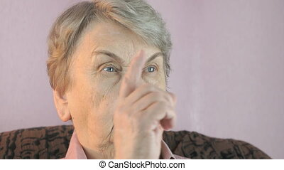 Aged woman waves her index finger in front of face - Aged...