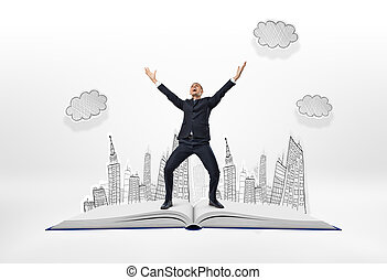 Happy businessman standing with his arms up on big opened...