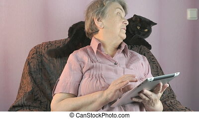 Aged woman looks at the black cat indoors - Aged woman 80s...