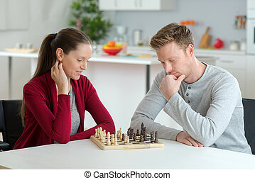 happy young couple playing chess in living room