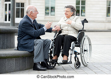old couple a man and woman sitting in wheelchair outdoors
