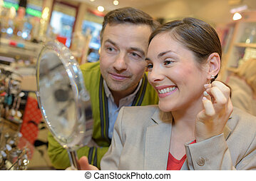 female client trying magnifying glasses at retail store