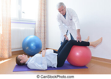 woman doing physiotherapy exercises with fitness ball