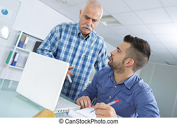 senior showing a trainee how to work on laptop