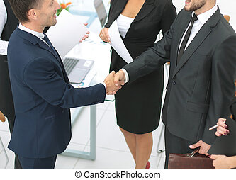 Diversity business team concluding contract with handshake...