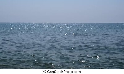 Clear blue sea water sparkles in the sun with sky and...