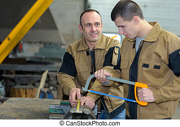 male workers sawing indoors
