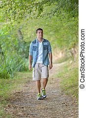 handsome man walking on forest path
