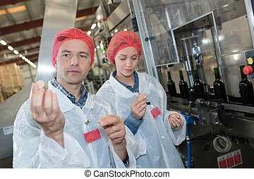 two workers analyzing a cork stopper of a bottle