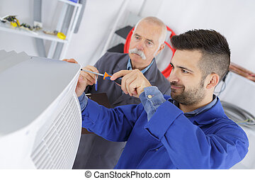 electrician and manager repairman fixing air conditioning