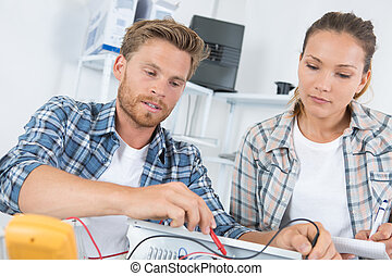 man fixing computer with woman watching