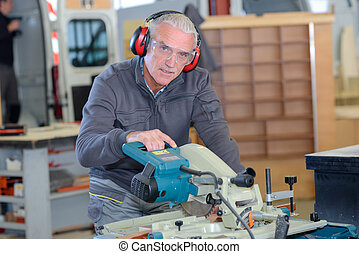 old-man man using a machine in a workshop