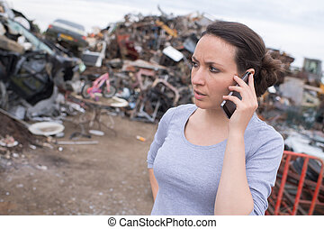 worried woman on the phone at a junk-yard