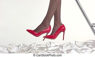 Legs wearing fishnets and heels. Red shoes with black...