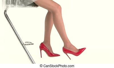 Legs wearing high heels. Woman sitting on bar chair. Look...
