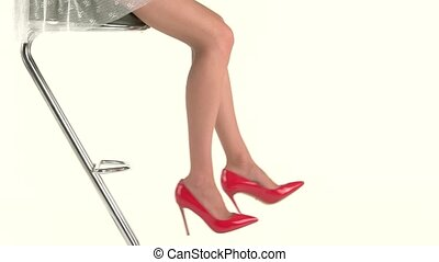 Legs in heels. Woman sits on bar chair. Charm and...