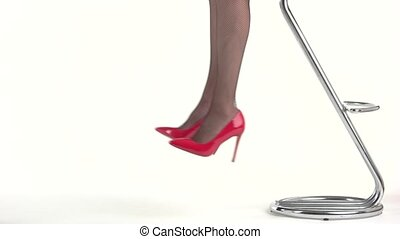 Lady's legs in high heels. Red glossy shoes. Femininity and...