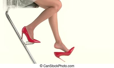Woman's legs in red shoes. Female sits on bar chair. Look...