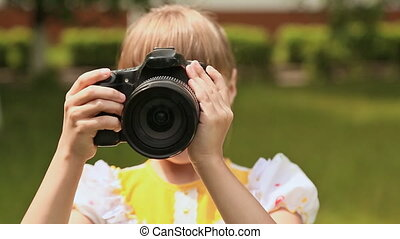 Girl with a professional digital camera on nature. - Girl...