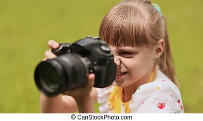 Teen girl making photo using the camera outdoors in the...